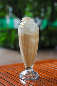A glass of ice coffee on the table in garden background